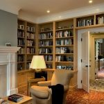 classic living room idea with creamy wing chair and fireplace and white siding and floor to ceiling bookshelves and patterned area rug