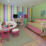 colorful-pastel-kids-bedroom-with-wide-papasan-chair-and-ottoman-with-white-cushion-and-pink-wood-and-pastel-color-carpet-on-the-wooden-floor