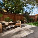 comfortable backyard patio design with concrete patio and rattan seatings and round table and green landscape
