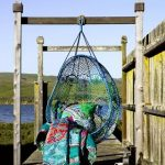 comfortable hanging chair on wooden deck aside lake view in blue color with green throw