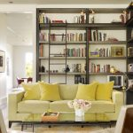 comfortable-sofas-with-yellow-cushions-and-white-carpet-also-flowers-centerpiece-on-glass-table-with-library-and-stair-on-transitional-living-room