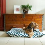 comfy and stylish dog bed  with an interesting motif decorated aside wooden table with plant on the pot and picture frame