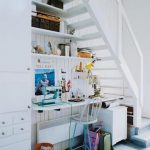 complete understairs with white wall racks and desk and blue white chair and orange bin and white file cabinet and white stairs