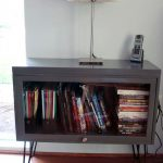 corner-small-metal-barrister-bookcase-with-one-door-and-white-table-lamp-and-handphone-above-it-and-many-books