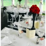 elegant-and-strong-centerpieces-with-red-roses-in-the-black-vases-on-the-red-black-and-white-wedding-reception-theme-also-all-the-white-chairs-tied-with-black-fabric
