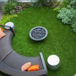 elegant backyard patio design idea with grassy meadow and gray half round bench and fire pit and white bench and wooden deck