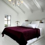 elegant classic white loft bedroom idea with purple sheet on white bedding with white wooden ceiling and chandelier