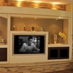 elegant in wall entertainment center with some storage and modern fireplace aside plus pictures on wall decoration