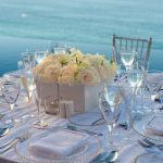 elegant-nice-and-stylish-beach-wedding-reception-tables-with-white-flowers-in-white-square-containers-and-white-chair-and-table-and-dirinking-glasses-and-wine-glasses