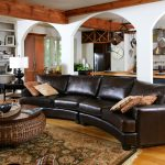 ethan allen leather furniture with dark brown leather  curved sofa together with round rattan coffee table with wooden top in traditional living room