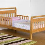 full size toddler bed with comfy bedding plus jute rug on wooden floor plus white painted wall and laundry basket