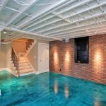 gorgeous aquatic blue painted flooring idea with brick wall and stairs and exposed wooden ceiling and poles
