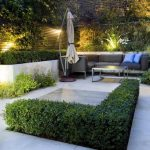 gorgeous backyard patio design with shrub with concrete patio with black sofa and blue throw pillows