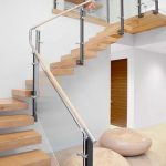 gorgeous beige stairs design with glass railing accent and round pouff beneath the stairs