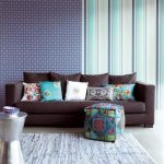 gorgeous combined wallpaper of  honeycomb with stripe pattern and brown sofa with patterned cushions and pouf and dried area rug