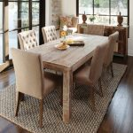 gorgeous small rectangular dining table made of oak with comfy beige chairs with sufted back and jute rug plus hardwood flooring