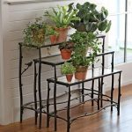 great indoor plant idea with stairs idea with wrought iron stand with orange pots with white brick siding on wooden floor