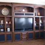 in wall entertainment center for living room ideas with decorative objects and media storage and solid hardwood floor and round end table