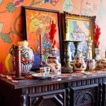 interior with color explosion and vintage black conssole table with carved style and frame photo and painted wall