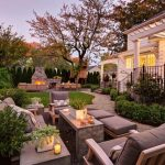luxurious and comfortable backyard patio dsign with creamy sofa and stone coffee tabke and box planter and shrub and pine tree