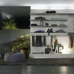 luxurious and spacious dressing room idea with white storage and gray floor and black area rug and gray pouf