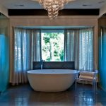 luxurious-bathroom-with-louis-ghost-chair-near-white-tub-under-crystal-pendant-lamp-and-white-curtain-covered-glass-windows