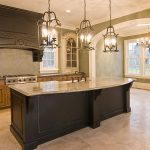 luxurious classic kitchen design with natural and black cabinetry and river gold granite idea with traditional lantern pendants and large glass window