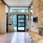 luxurious interior design with stone wall accenta nd glass image front door idea with white flooring and pendants