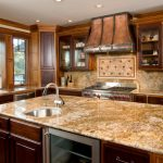 luxurious mediterranian kitchen design with dark wooden cabinetry with river gold granite countertop and luxurous lighting and open plan