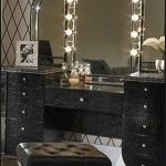 makeup-vanity-set-with-lighted-mirror-and-Hollywood-Vanity-black-table-with-black-stool-on-the-fluffy-white-carpet-and-picture-and-white-flower