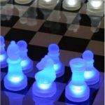 Modern LED Chess Set With Glowing White And Blue Pieces On The Chessboard And In The Dark Place