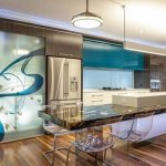 modern and large kitchen design with extended bar table with turquoise accent with pendant and wooden flooring