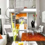 modern and small kitchen studio idea with small corner dining spae with white sofa and lily decoration beneath stairs and wooden floor and caramel tone area rug