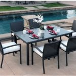 modern-and-stylish-outdoor-dining-rable-and-chairs-near-the-pool-with-beautiful-white-flowers-as-centerpiece-