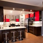 modern kitchen design with brown kitchen set and red accent and black modern stools and wooden laminated flooring