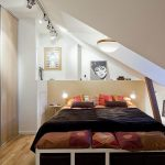 modern loft bedroom idea with brown black bedding decoration beneath sloping concreet ceiling with skylight