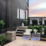 modern minimalist courtyard for private house design with tall black wooden siding and wire seating and white chair and stairs and wooden patio