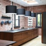 modern refined kitchen studio design idea with industrial style with red brick wall accent and wooden island and big black shaded pendants and skylight