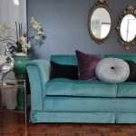 modern turquoise velvet fabric sofa design with purple black and gray cushions with vintage wall mirrors and vassed flower
