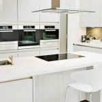 modern white kitchen design with white island with white stools and smokestack and cream backsplash