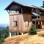 on slope area small rustic cabin house design with open plan overlooking the distance