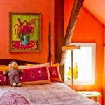 orange interior design ith color explosion of loft bedroom with rustic wooden accent and pink bedding