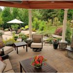 outdoor backyard patio design with stone fireplace and creamy sofa and wooden table and concrete patio and wooden pergola