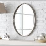 oval mirror with crafted nickel frame a table lamp with light cream head
