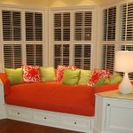 playful home decoration with window seats with storage completed with orange upholstery  and green cushion with double table lamps plus cool bay windows