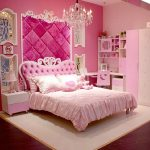 Queen Like Princess Bedding Idea With Tufted Crown Headboard And Pink Board Panel And Chandelier And White Area Rug And Wall Shelves And Wooden Floor