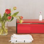 red-brabantia-bread-box-and-fall-front-with-fingerprint-proof-and-matt-steel-on-the-wooden-table-near-white-kitchen-towels-and-red-flowers-in-vase-