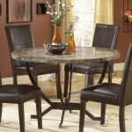 round granite dining table set with adorable table base plus four brown leather dining chairs and pretty vase as a centerpiece