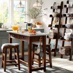 rustic-wooden-ladder-shelf-in-the-modern-kitchen-for-storing-plates-glasses-mugs-and-bottles-near-wooden-kitchen-island-and-wooden-chairs