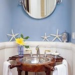 sea-themed-bathroom-with-mirror-on-the-blue-wall-with-starfishes-and-yellow-flower-and-white-towels-on-the-navigator-design-of-the-sink